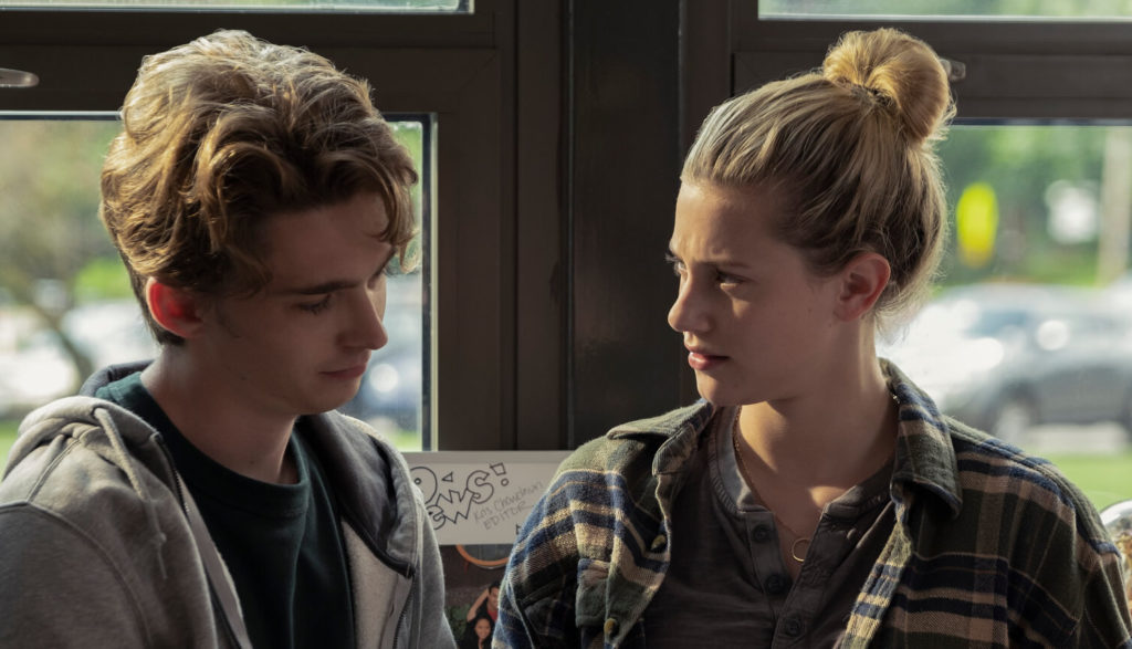 Two teens look at each other.
