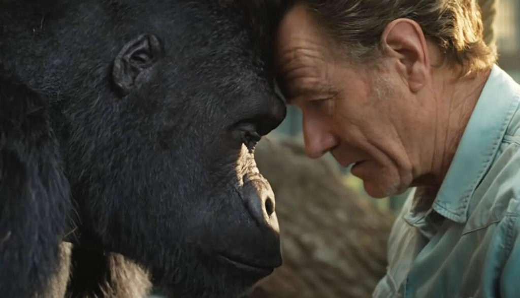 A man and a gorilla touch foreheads.