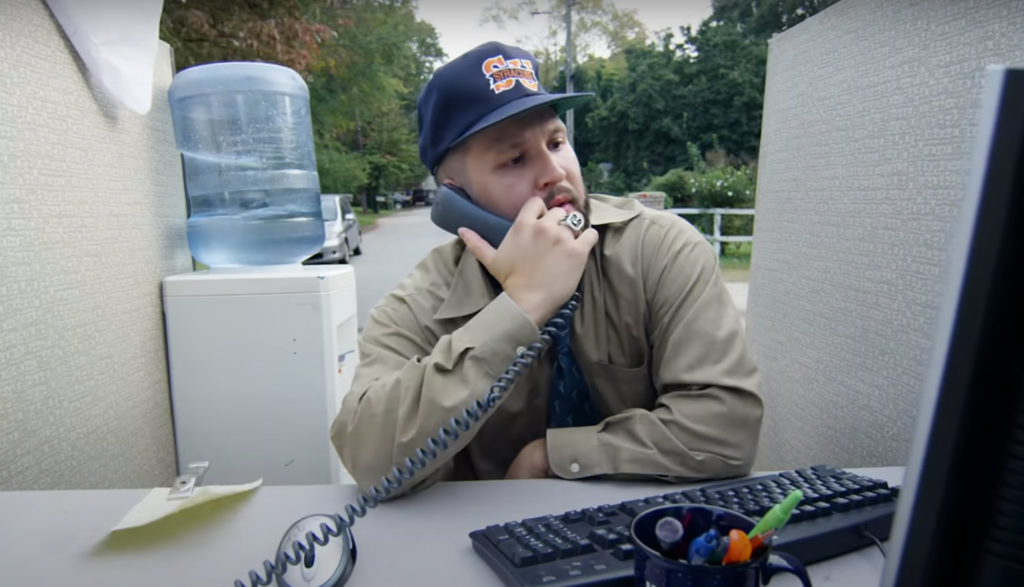 Rapper Andy Mineo sings about life's stress while sitting at a computer with a phone to his ear.