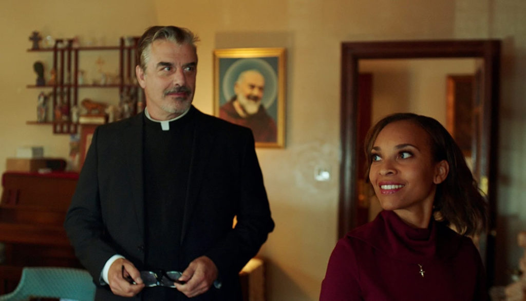A woman smiles as she talks with her Catholic priest.