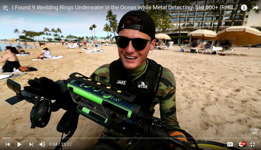 YouTuber Jake Koehler stands on a beach holding a waterproof metal detector.