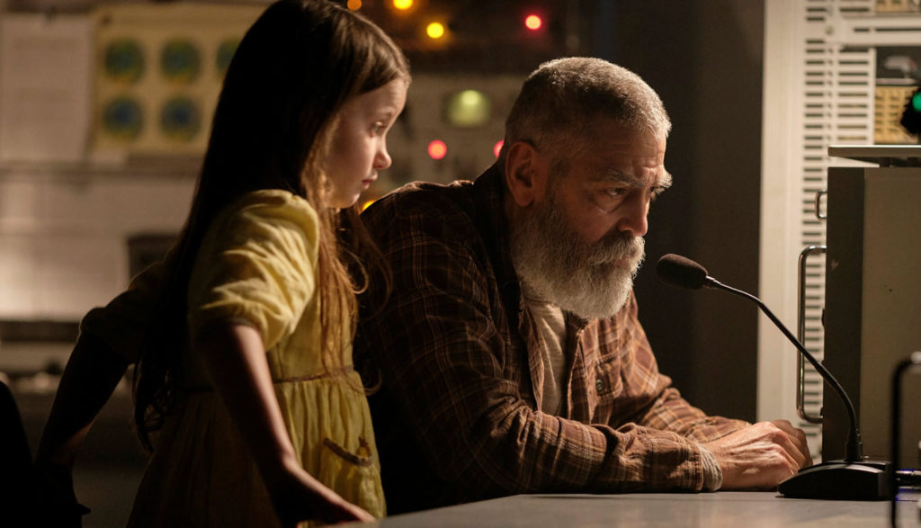 George Clooney and a young girl stare at something at a desk in The Midnight Sky.