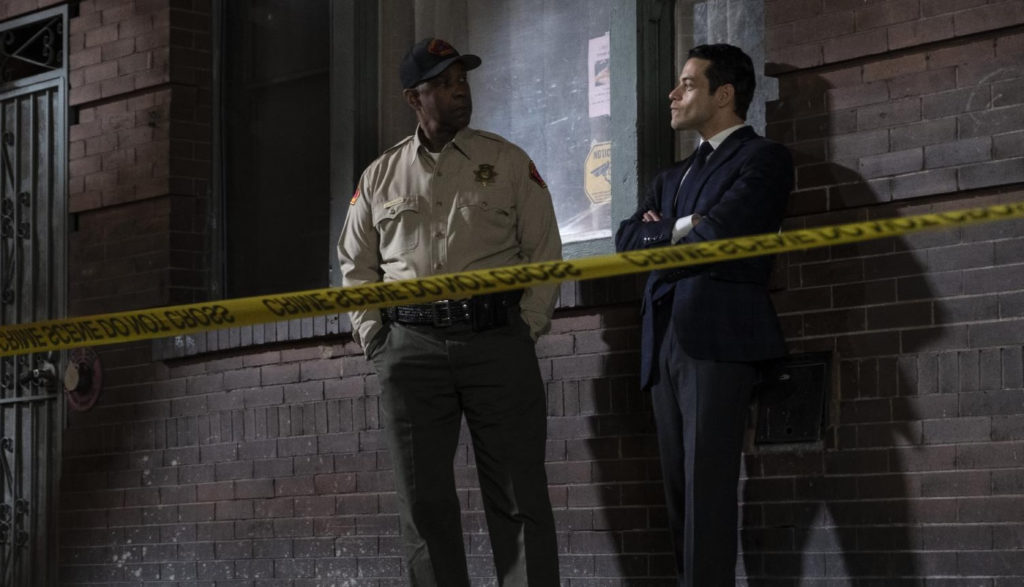 A police officer and a detective stand near a building and a crime scene.