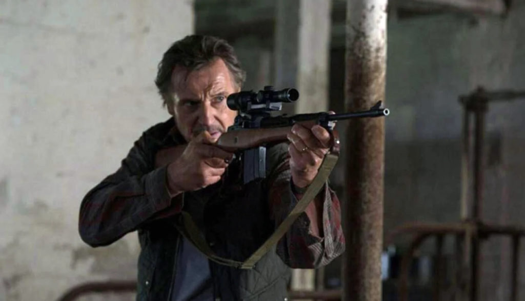 Liam Neeson shoulders a rifle and aims in The Marksman.