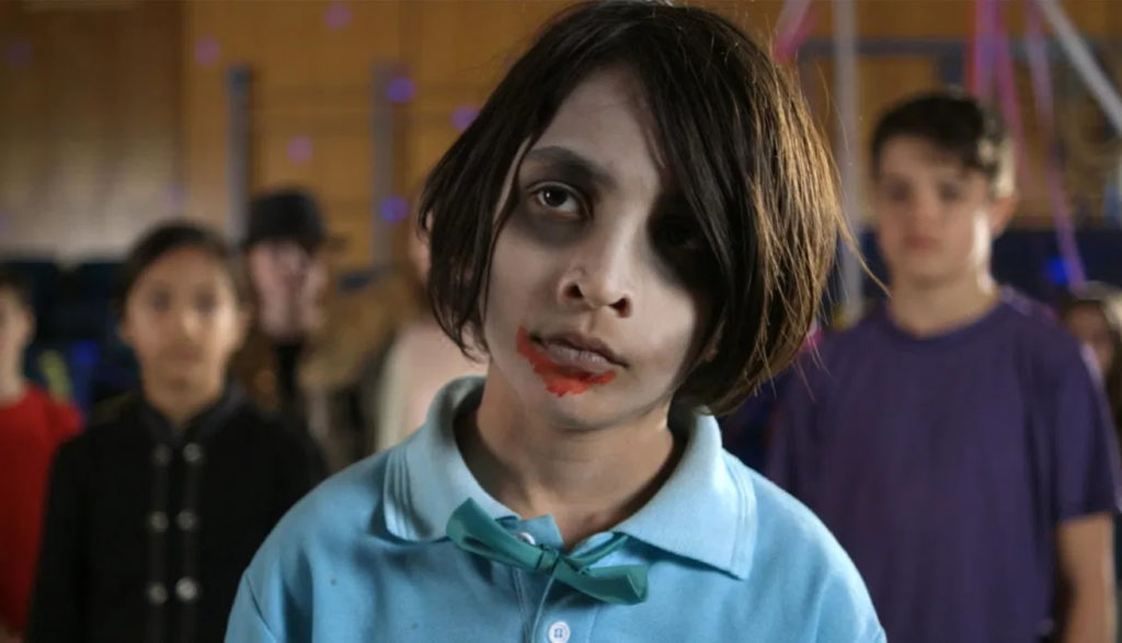 A tween zombie boy stares at the camera.