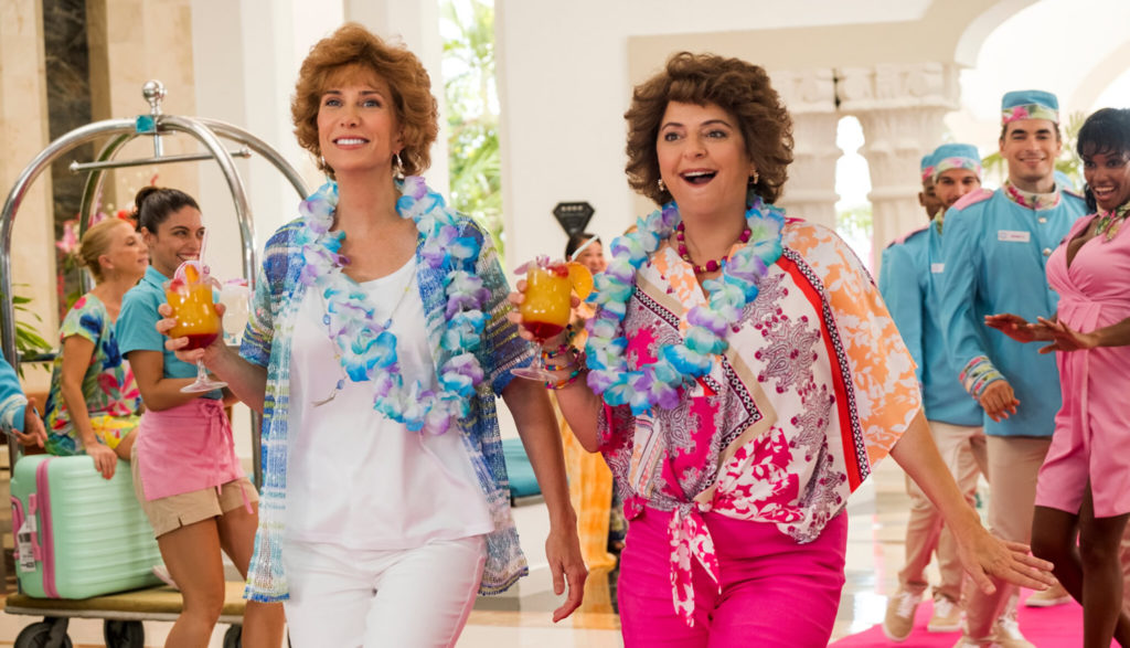 Two middle-aged women arrive at a posh tropical resort hotel, with huge smiles on their faces.