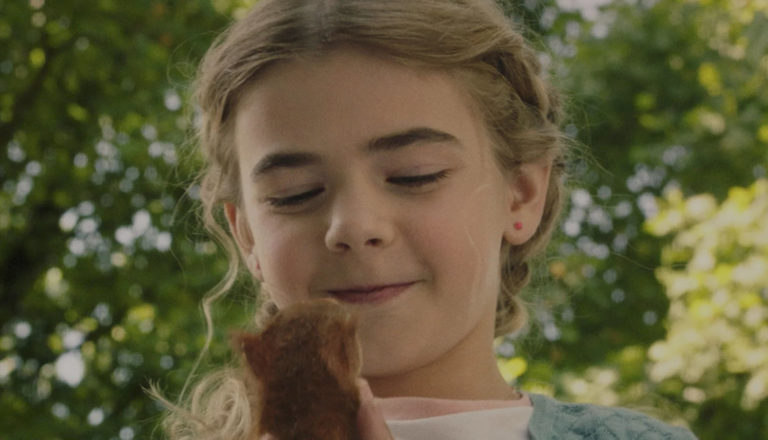 A young girl holds and smiles at a squirrel in her hands.