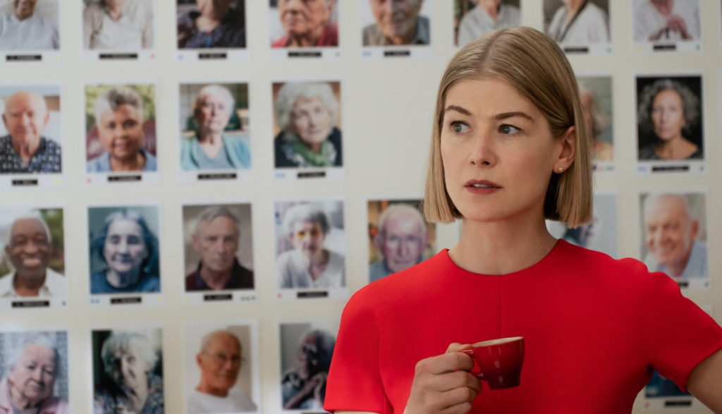 A woman stands with a cup of tea in front of portrait photos of elderly people behind her.