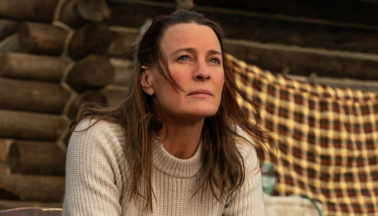 A woman (played by actress Robin Wright) sits in front of a log cabin with a thoughtful expression on her face.