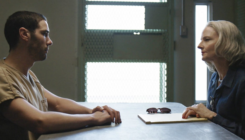 A female lawyer talks with her client across a table in a prison.