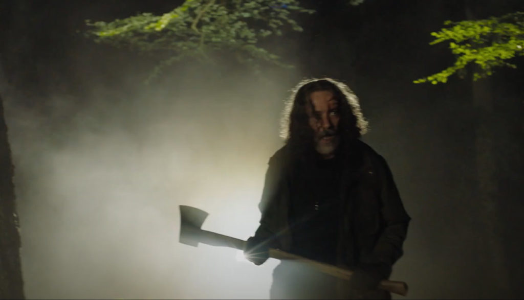 A creepy man with an ax walks through a poorly lit forest.