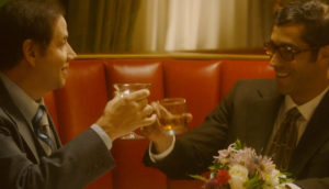 Two men celebrate a victory with a toast.