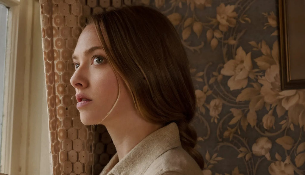 A woman (played by actress Amanda Seyfried) looks pensively out a window in the movie 'Thinks Heard & Seen.'
