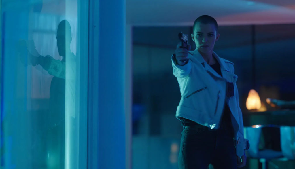A woman points a pistol at someone in a dark room.