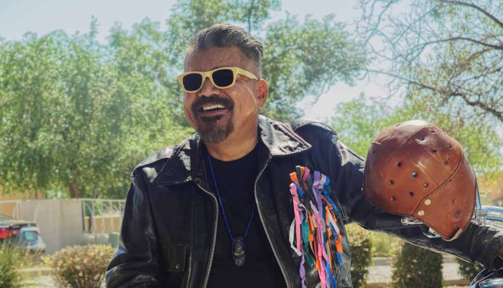 George Lopez plays an angel named Herb, and we see him here in sunglasses, leather and holding an old-school football helmet.