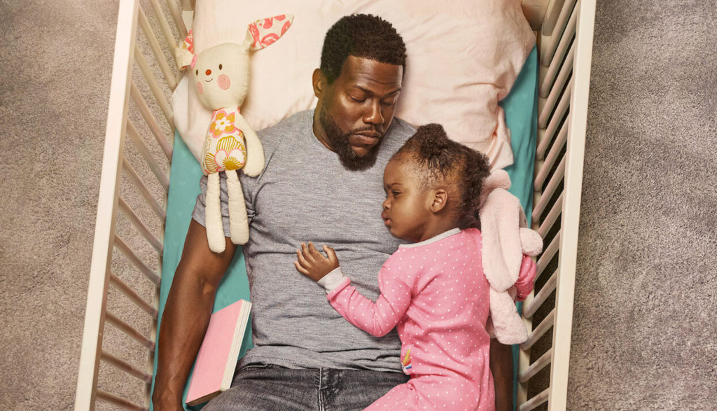 Father cradling his daughter in her crib in Fatherhood